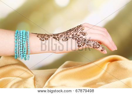 Process of applying Mehndi on female hand, close up
