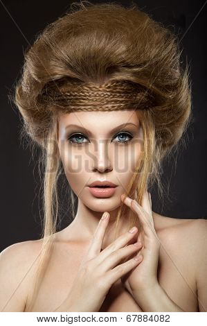 Beautiful red-haired girl with perfect skin and an unusual hairstyle.