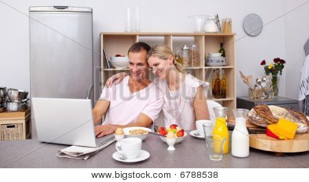 Happy Couple Using A Laptop While Having Breakfast