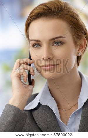 Closeup portrait of attractive young businesswoman talking on mobilephone, smiling, looking away.