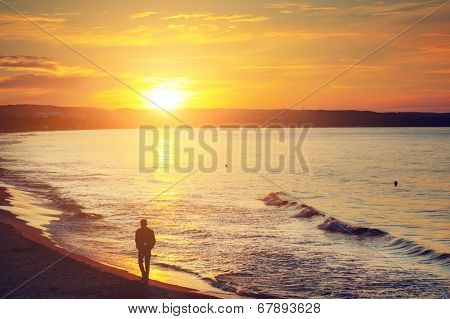 Man walking alone on the beach at sunset. Calm sea with rippling waves.
