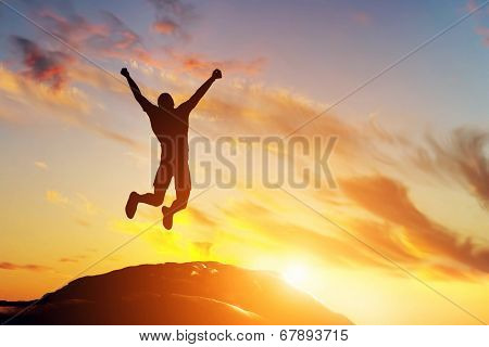 Happy man jumping for joy on the peak of the mountain, cliff at sunset. Success, winner, happiness