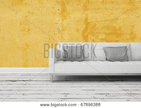 Modern sofa in front of a yellow wall on a rustic wooden floor painted white with copyspace