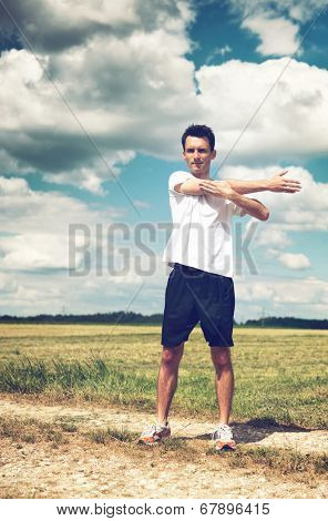 Young determined man wearing summer sportswear and standing up while performing stretching exercise for the right arm, outdoors, at the countryside, in a warm day