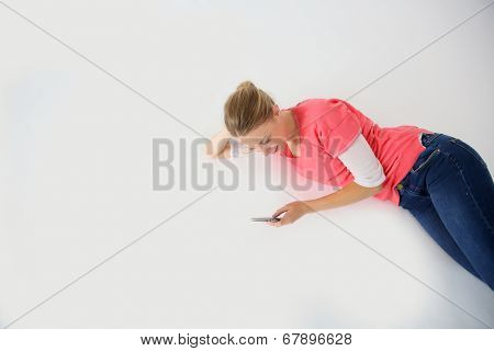 Young woman laying on floor with smartphone, isolated