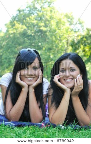 Two Smiling Sisters Lying Outdoors In Grass