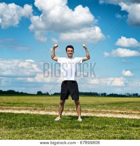 Healthy fit sportsman flexing his arms as he stands in an open rural field alongside a track in his sportswear smiling as he limbers up for his workout and training showing off his muscles