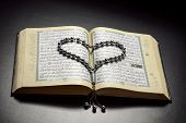 foto of islamic religious holy book  - Islamic Book Holy Quran with Heart Shaped Subha on Black Background - JPG