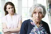 stock photo of senior adult  - Portrait Of Serious Senior Woman With Worried Adult Daughter At Home - JPG