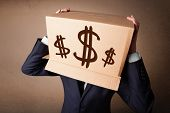 stock photo of faceless  - Businessman standing and gesturing with a cardboard box on his head with dollar signs - JPG