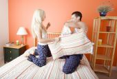 stock photo of shelving unit  - Young couple facing each other kneeling on bed having a pillow fight - JPG