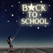 stock photo of reach the stars  - Portrait of young female student pulling down a back to school text and the stars with rope - JPG