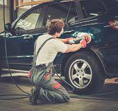 stock photo of machine  - Serviceman polishing car body with machine  in a workshop - JPG