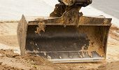 stock photo of bobcat  - front bucket of a bobcat moving dirt for a new driveway - JPG