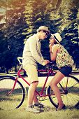 image of amor  - Happy young couple in summer park rides a bike - JPG