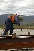 picture of sandblasting  - tradesman sandblasting steel beams for building project - JPG