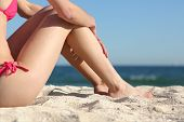 stock photo of sunbather  - Sunbather woman legs sitting on the sand of the beach resting with the sea in the background - JPG