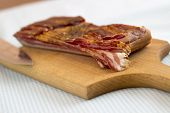 pic of bacon strips  - Cutting bacon into strips on a cutting board - JPG