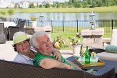 pic of settee  - Affectionate elderly couple enjoy a relaxing day on the patio sitting close together on a wicker settee overlooking a scenic pond turning to look back at the camera with a smile - JPG