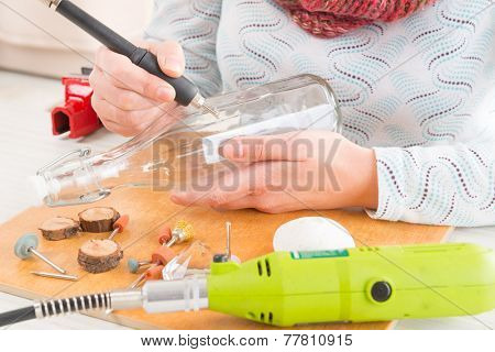 Woman using a high speed rotary multi tool to engrave ornament on the bottle