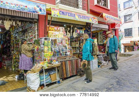 LA PAZ, BOLIVIA, MAY 8, 2014: Tourists  watch the display of amulets and aphrodisiacs on outdoor stall, Witches Market