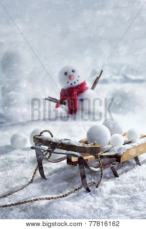 Wooden sleigh and snowballs with snowman and wintery background