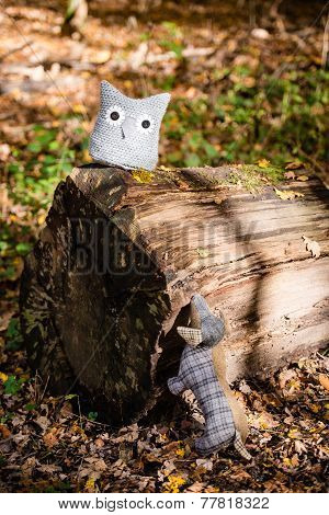Soft toy dog is chasing an owl in autumn forest