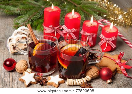 Glasses of red mulled wine on table with burning candles and christmas decorations