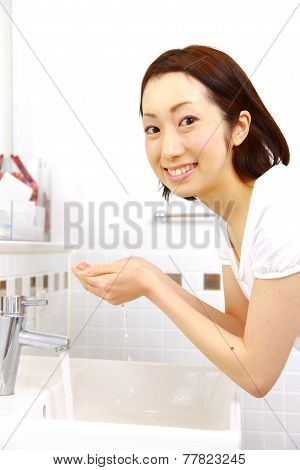 woman washes her face