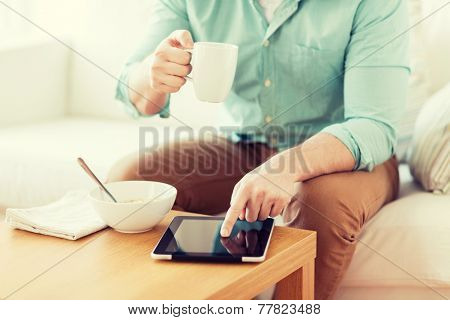 technology, home, drinks, food and lifestyle concept - close up of man with tablet pc computer and cup of coffee having breakfast at home