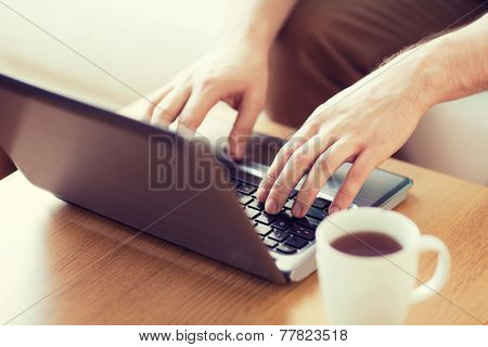 technology, home, drinks and lifestyle concept - close up of man with laptop and cup of coffee at home