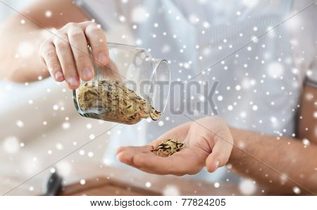 cooking, people and home concept - close up of man emptying jar with mixture of white and wild black rice in kitchen