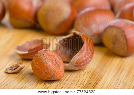 Hazelnut kernel and its shell on wooden background
