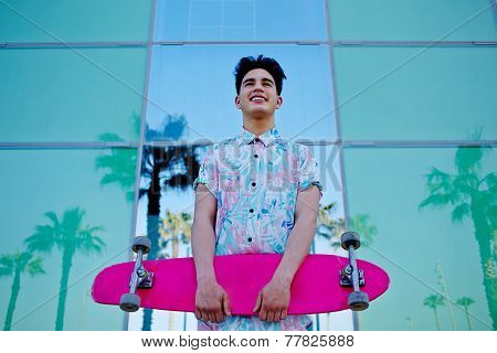 Stylish teenager man smiling holding pink long-board