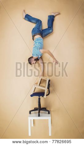 Man on a pile of chairs