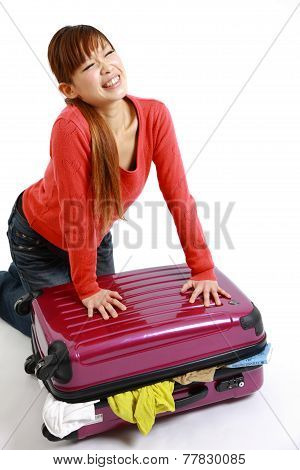 young Japanese woman with overloaded Suitcase