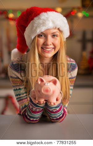 Smiling Teenager Girl In Santa Hat Showing Piggy Bank