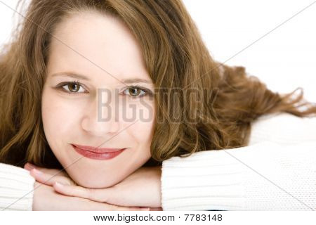 Young woman lying on floor with chin on hands is smiling happy into camera.