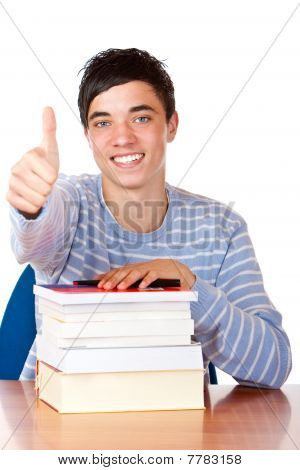 Young happy male student is smiling and leaning on his study books.