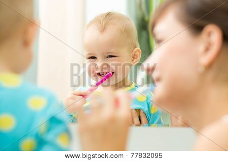 mother and kid look at mirror during teeth brushing