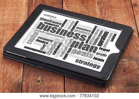 business plan word cloud on a digital tablet against weathered wood