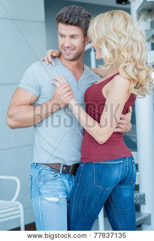 Sexy Happy Couple Wearing Casual Clothing Dancing with Arms Around Each Other