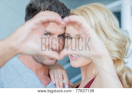 Couple in Love Looking at Camera Through Hands Making Heart Shape