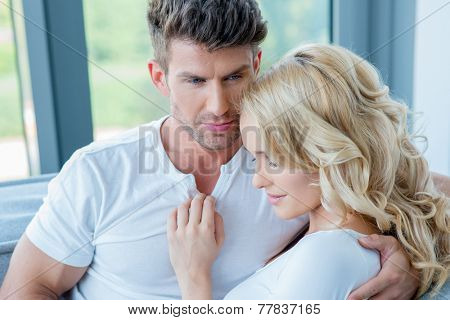 Close up Romantic Young White Couple in Casual White Shirts  Sitting near the Window with Woman Leaning on Man's Arm.
