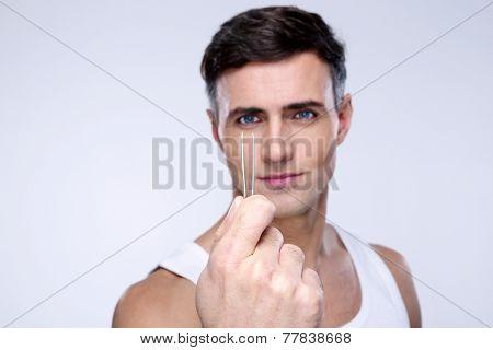Handsome man holding tweezers. Focus on tweezers