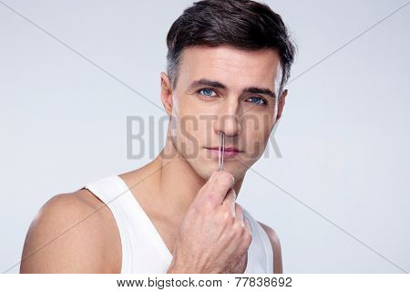 Man pucking nose hair with tweezers over gray background