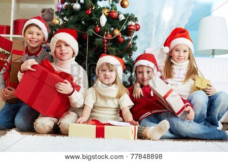 Group of adorable kids in Santa caps holding giftboxes