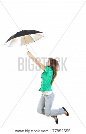Girl In Green Shirt And Gray Jeans Pants With Umbrella Jumping In Air Up
