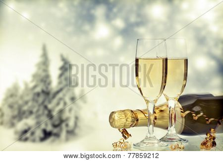 Glasses with champagne and bottle, snow cowered pine trees in the background