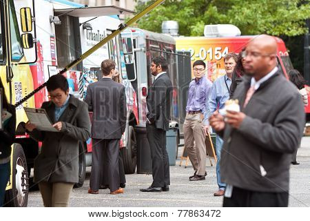 People Wait In Line To Order Meals From Food Trucks